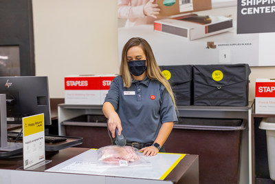 Staples employee preparing returned item to be shipped in a Happy Returns reusable tote.